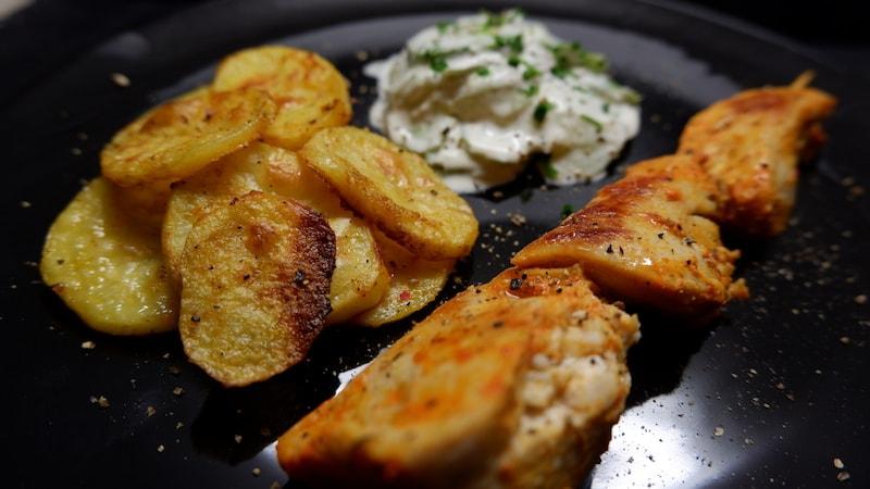 Knusprige Kartoffelscheiben mit Hähnchenspieß und Gurkensalat
